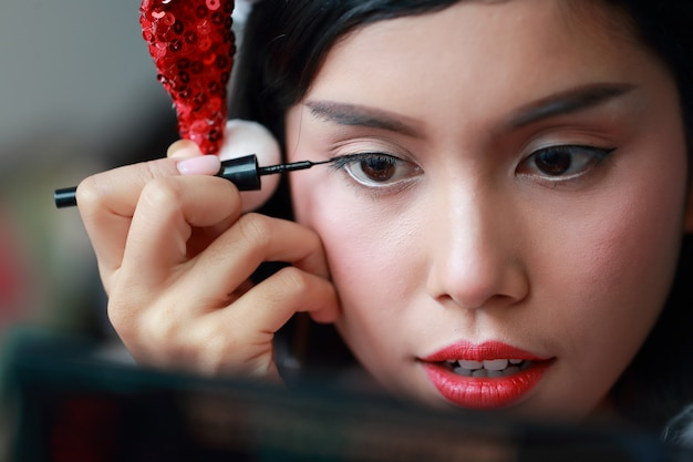 Young asian santa girl applying eye shadow on beautiful face Premium Photo