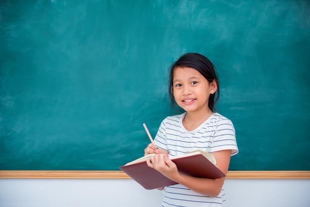 Young asian schoolgirl smiling in front of chalkboard Premium Photo