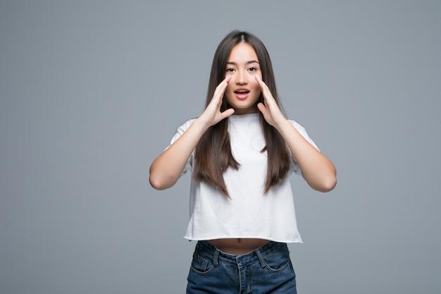 Giovane urlo asiatico rumoroso isolato su sfondo grigio Foto Gratuite