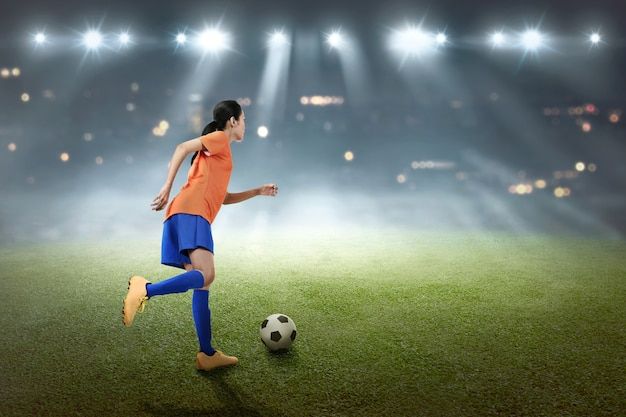 Young asian soccer player woman kick the ball Premium Photo