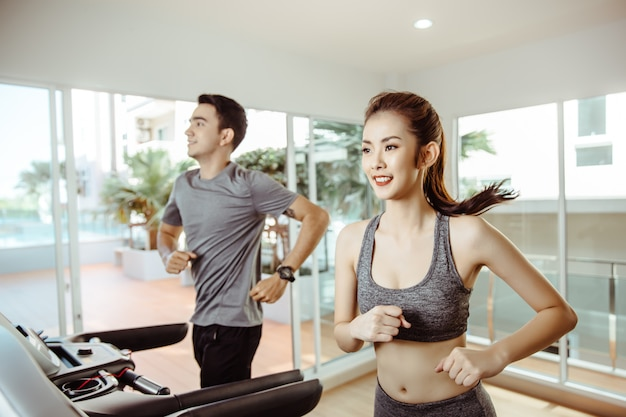 Young asian sporty women run on machine in the gym centre Premium Photo