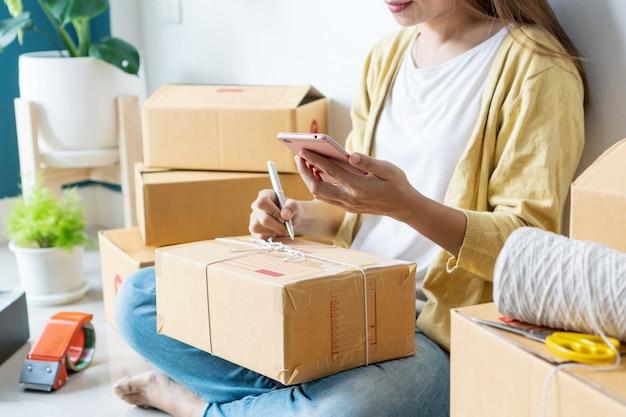 若いアジア人は、中小企業のオーナーが職場の段ボール箱に住所を書き始めます。オンライン販売、eコマース、配送コンセプト Premium写真