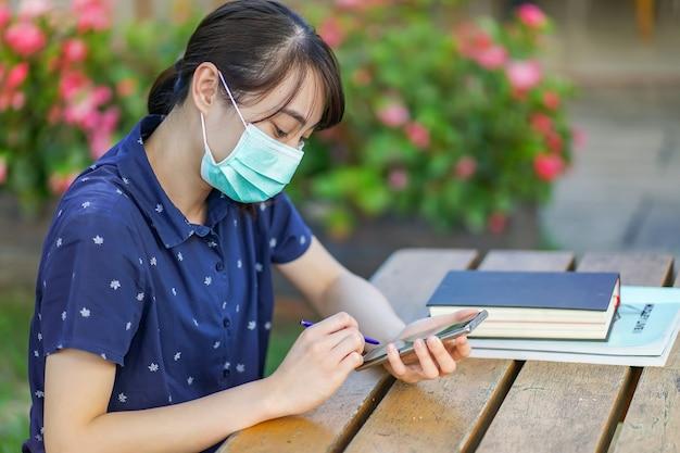 本と庭のベンチに座っている間医療マスクを着用し、スマートフォンを押し、画面を見て、アプリまたはメッセージングを使用して若いアジア学生女性。 covid-19の後の新しい通常のコンセプト Premium写真