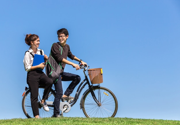 Young asian students ride a bicycle in university with nature ba Premium Photo