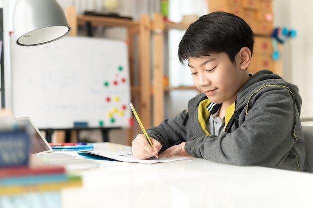 Young asian teenage student doing homework Premium Photo