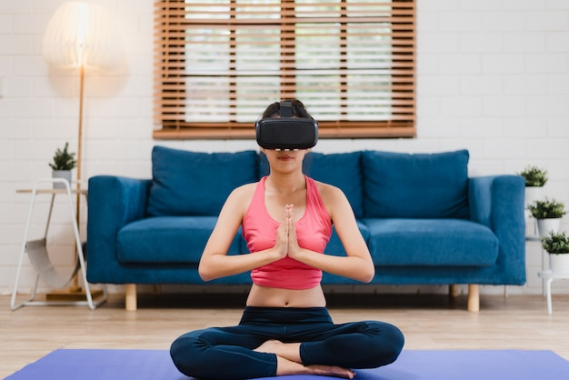 Young asian teenager woman using virtual reality simulator while practicing yoga in living room Free Photo