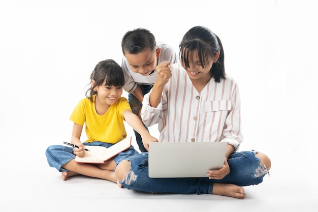 Young asian thai  kids, boy and girl learning and  looking on laptop by technology and multimedia Premium Photo