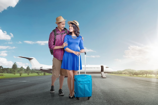 Young asian tourist couple with luggage going traveling with airplane Premium Photo