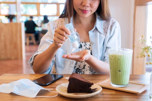 Молодая азиатская женщина, применяющая дезинфицирующее средство для рук, чтобы очистить руку перед едой. концепция здравоохранения. Premium Фотографии