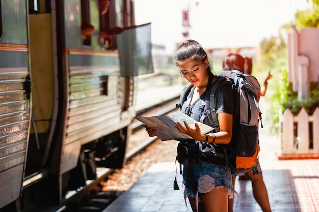 Young asian woman backpacker and traveling looking map Premium Photo