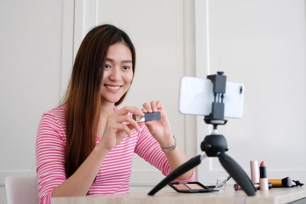 スマートフォンで録画中にビデオチュートリアルを構成する方法を示している若いアジア人女性の美人ブロガー Premium写真