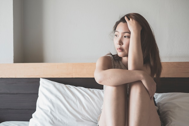 Young asian woman on a bed with sadness Premium Photo