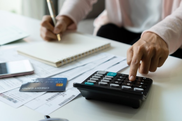 Young asian woman calculating monthy expense at her desk. home saving concept. financial and installment payment concept. close up. Premium Photo