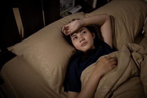 Young asian woman cannot sleep insomnia late at night. can't sleep. sleep apnea or stress. sleep disorder concept. Premium Photo