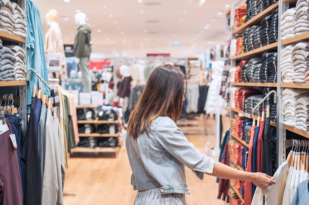Young asian woman choosing clothes in clothing store at the mall, woman shopping lifestyle concept Premium Photo