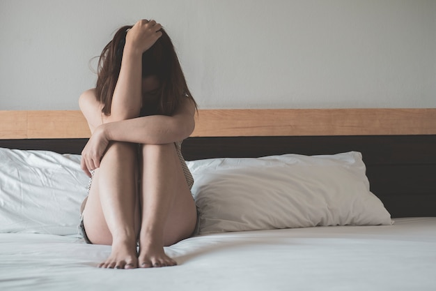 Young asian woman covering her face sitting on a bed with sadness Premium Photo