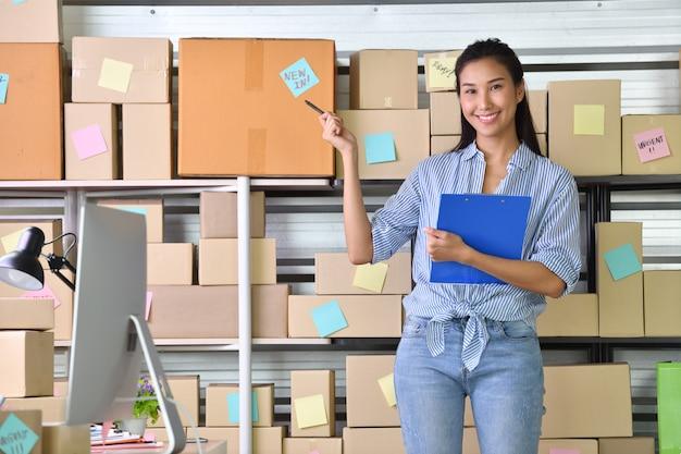 Молодая азиатская женщина-предприниматель, владелец бизнеса, работающий дома для покупок в интернете и готовящий пакетный продукт Premium Фотографии
