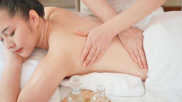 Молодая азиатская женщина получая расслабляющий массаж масла на салоне курорта красоты. массаж для здоровья | Премиум Фото
