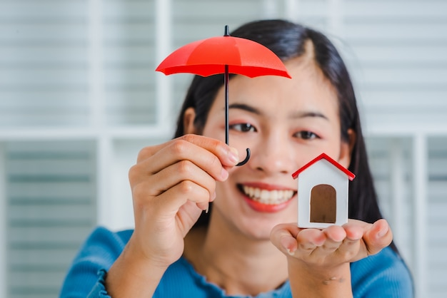 Young asian woman hand hold umbrella toy to protect the home. Premium Photo
