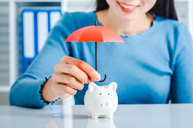 Young asian woman hand hold umbrella toy to protect piggy bank. Premium Photo