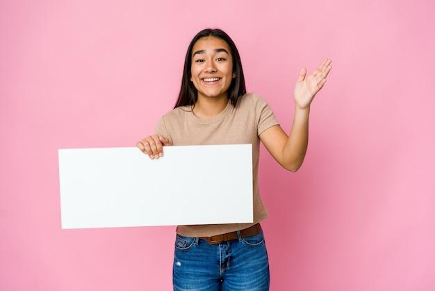 즐거운 놀라움을 받고 고립 된 벽 위에 흰색 뭔가 빈 종이를 들고 젊은 아시아 여자, 흥분하고 손을 올리는 프리미엄 사진