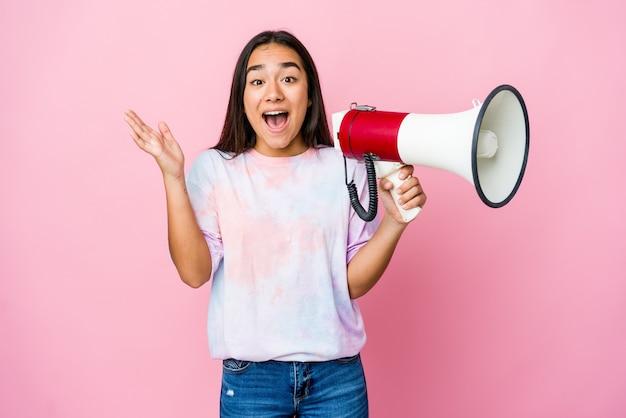 즐거운 놀라움을 받고, 흥분하고 손을 올리는 분홍색 벽에 고립 된 확성기를 들고 젊은 아시아 여자 프리미엄 사진