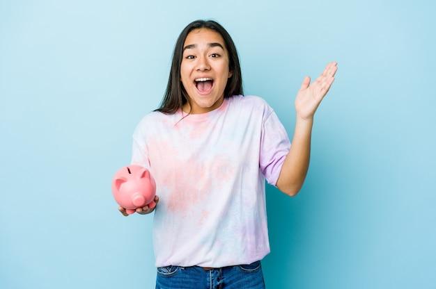 즐거운 놀라움을 받고, 흥분하고 손을 올리는 고립 된 벽 위에 분홍색 은행을 들고 젊은 아시아 여자 프리미엄 사진