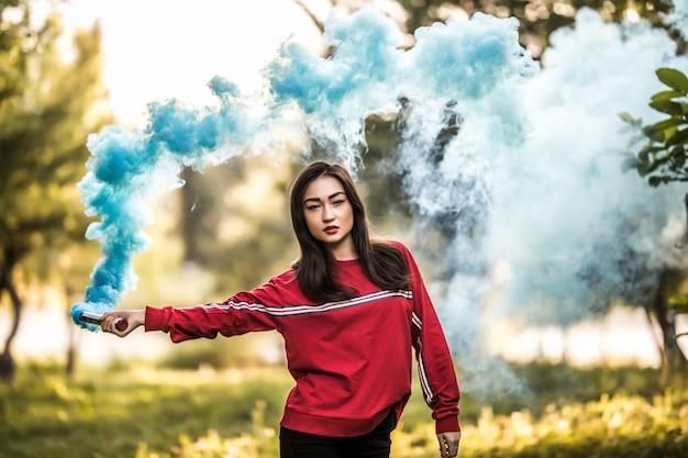屋外の公園で青のカラフルな煙爆弾を保持している若いアジア女性。青い煙の広がり 無料写真