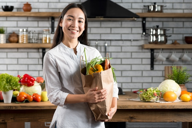 Young asian woman holding brown grocery bag with vegetables Free Photo