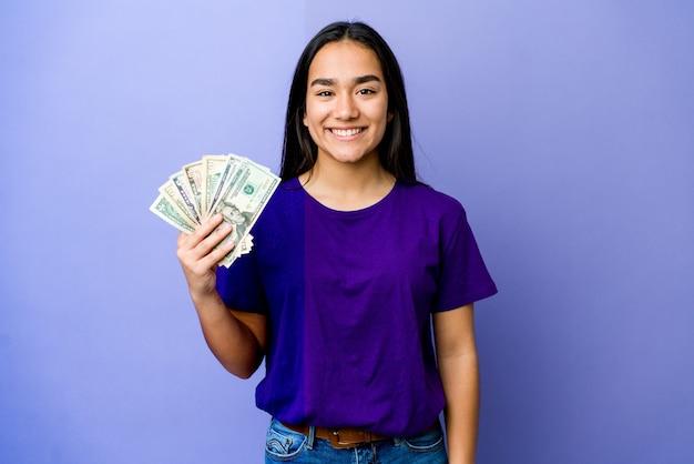 행복 하 고 웃 고 쾌활 한 보라색 벽에 고립 된 돈을 들고 젊은 아시아 여자 프리미엄 사진