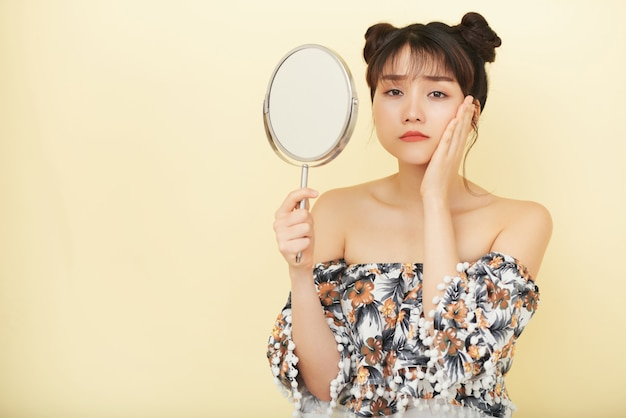 Young asian woman holding up hand mirror and looking at camera with unhappy face Free Photo