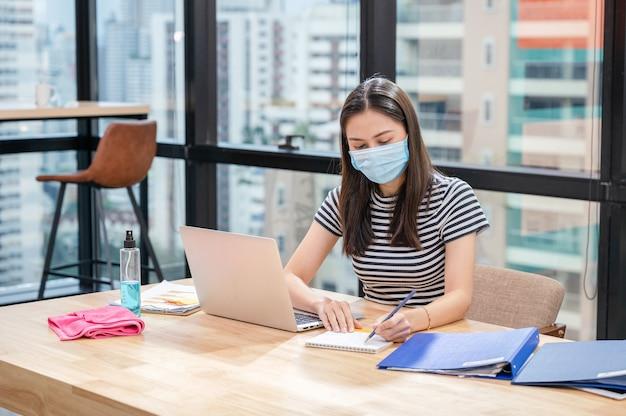フェイスマスクと新しい通常のオフィスでカレンダーのスケジュールのメモとカジュアルな若いアジアの女性 Premium写真