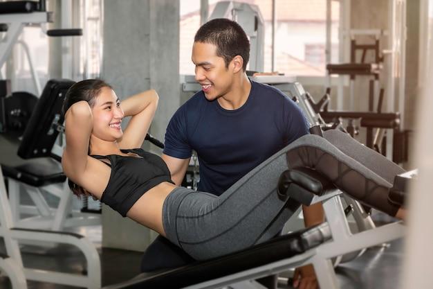 スポーツウェアトレーニングの若いアジア女性は、フィットネスジムで男性トレーナーと座ります。 Premium写真