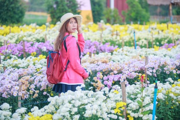 Молодая азиатская женщина в саде хризантемы. Premium Фотографии