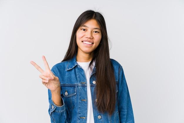 Молодая азиатская женщина радостная и беззаботная показывая символ мира с пальцами Premium Фотографии