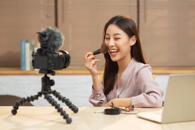 Молодая азиатская женщина смотрит на запись камеры, снимая свое самообучение из косметики онлайн Premium Фотографии