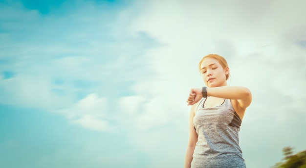 Young asian woman looking the sports watch and checking her performance after jogging run. Premium Photo