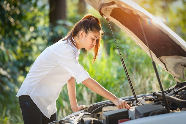 Young asian woman looks under the hood of a broken car. Premium Photo