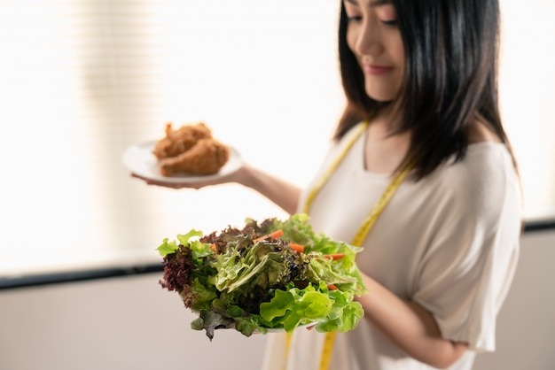 Young asian woman  lose weight choosing between vegetable salad and junk food fried chicken in dishes on her hand Premium Photo
