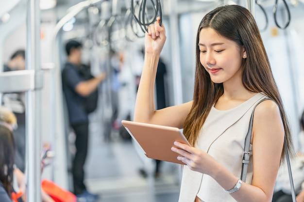 Young asian woman passenger using mutimedia player via technology tablet Premium Photo