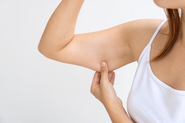 Молодая азиатская женщина зажимает дряблую кожу или дряблость на плече на белой стене Premium Фотографии