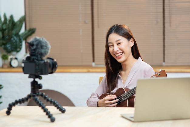 Молодая азиатская женщина играет и преподает на гитаре онлайн во время записи на камеру Premium Фотографии