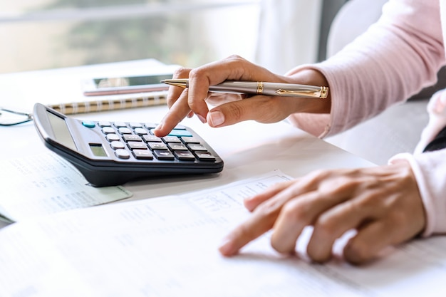 Запись молодой азиатской женщины доходов и расходов на ее столе. концепция сохранения дома. закрыть вверх Premium Фотографии
