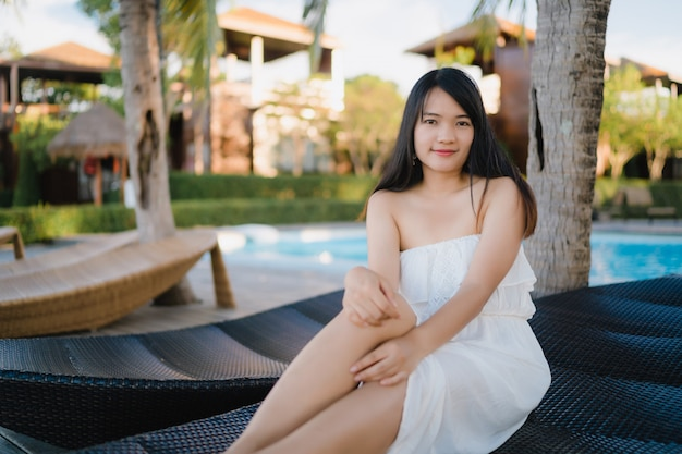 Young asian woman relax near swimming pool in hotel, beautiful female happy relax near sea. Free Photo