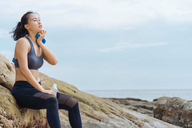 Young asian woman runner resting after workout running on the beach Premium Photo