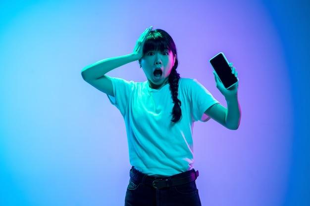 Ritratto di giovane donna asiatica su sfondo sfumato blu-viola studio in luce al neon. concetto di gioventù, emozioni umane, espressione facciale, vendite, annuncio. bellissima modella bruna. Foto Gratuite