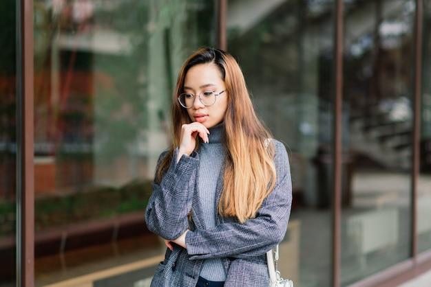 젊은 아시아 여자, 저녁에 도시에서 슬픈 얼굴 초상화 프리미엄 사진