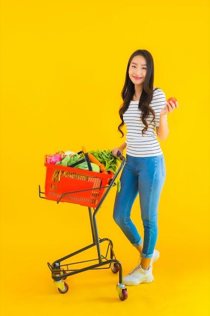 スーパーマーケットとカートから食料品を買い物若いアジア女性 無料写真