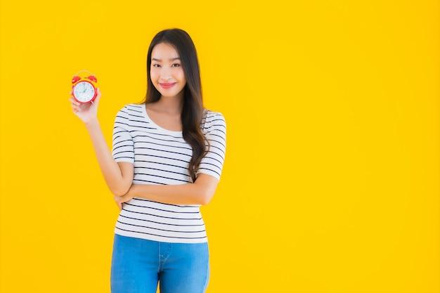 若いアジアの女性の時計またはアラーム 無料写真