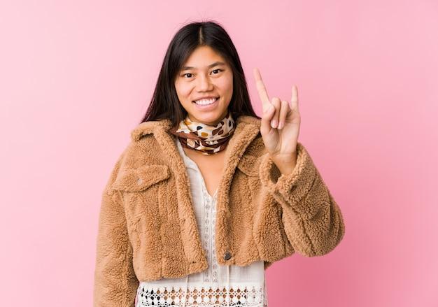 Молодая азиатская женщина показывая жест рожков Premium Фотографии